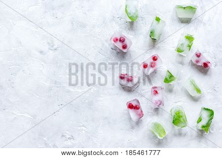 Ice cubes with fresh berries and mint on stone table background top view mock up