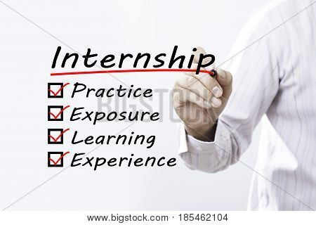 Businessman hand writing Internship benefits with red marker on transparent wipe board business/ education concept.