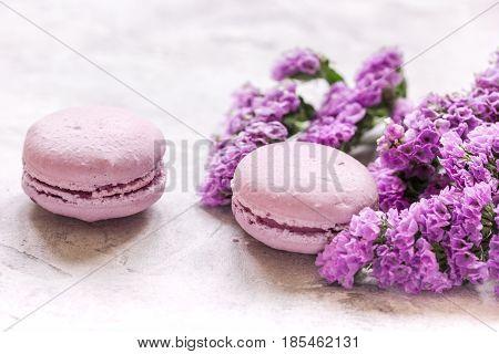 macaroons and mauve flowers for light female breakfast on white desk background