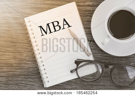 Concept MBA message on notebook with glasses pencil and coffee cup on wooden table.