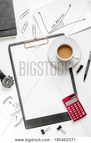 set for business strategy with sketch board, graphics and cup of coffee on white office table background top view mock up