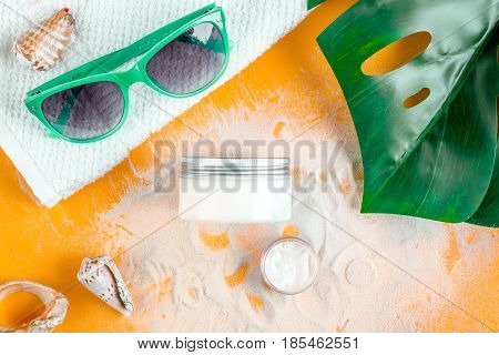 cream and lotion cosmetic for sun protection and glasses in a woman hygiene concept on orange background top view