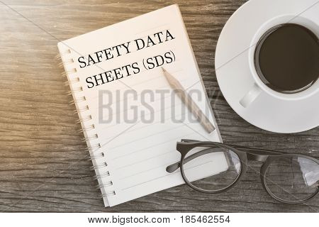 Concept SAFETY DATA SHEETS (SDS) message on notebook with glasses pencil and coffee cup on wooden table. Safety & Health.