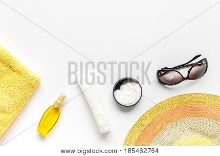 Towel, sun lotion, glasses for summer rest on white background top view space for text