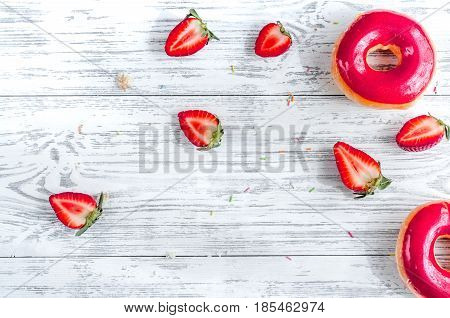 tasty lunch with colorful donuts and strawberry on wooden table background top view mock up