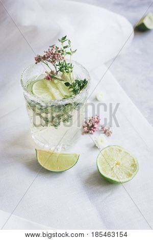 making cocktails in glasses with lime and herbs at home on stone kitchen desk background