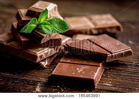 black and milk chocolate pieces with mint on wooden table background