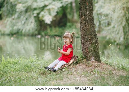 girl in a red dress walking and playing in the summer park