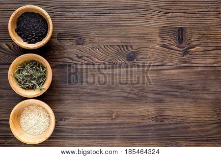Dry colorful spices, salt, pepper for homemade dinner on kitchen wooden table background top view mockup