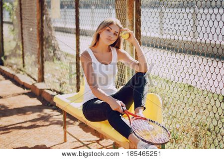 girl sitting on a bench and holding a tennis racket and tennis ball