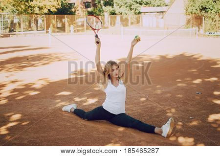 girl in a park on the tennis ground holding a tennis racket