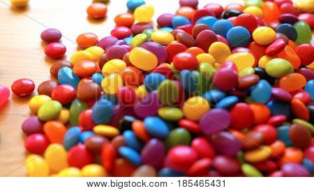 Colorful chocolate candies falling on table in naural window light shallow DOF.