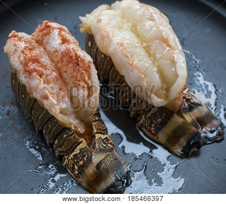 Raw lobster tail  food on a black background