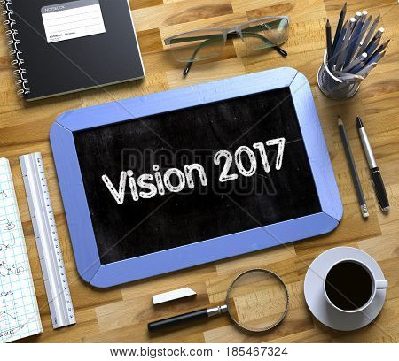 Vision 2017 on Small Chalkboard. Vision 2017 Handwritten on Blue Chalkboard. Top View Composition with Small Chalkboard on Working Table with Office Supplies Around. 3d Rendering.