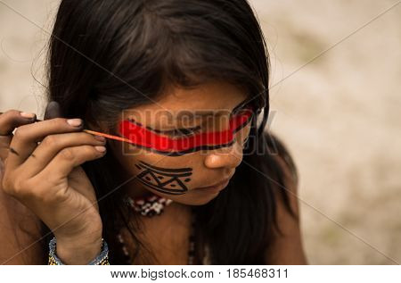 Native Brazilian girl from Tupi Guarani tribe painting her face, Brazil