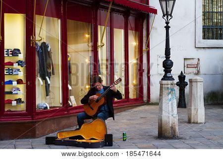 VIENNA-MARCH 30 2017. Street musitian sitting and playing guitar for tourists Kohlmarkt 11. March 30 2017 Vienna Austria.