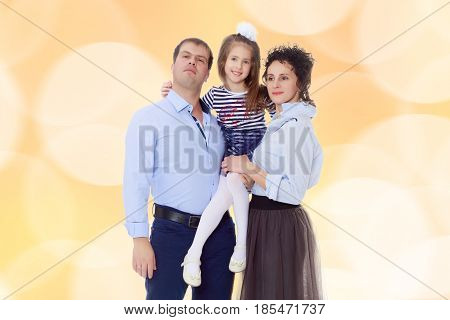 Happy young family, mom dad and little daughter.Parents keep the girl in her arms , and she hugs their neck.Brown festive, Christmas background with white snowflakes, circles.