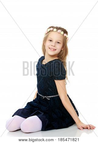 Beautiful little girl dressed in blue dress poses for the camera sitting on the floor .Isolated on white background.