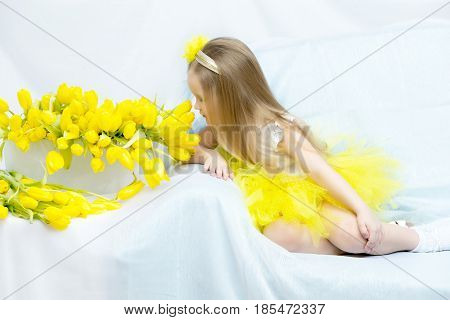 Cute little girl sitting on the couch beside a large bouquet of bright yellow tulips.The girl bowed her head over the flowers and sniffs them.