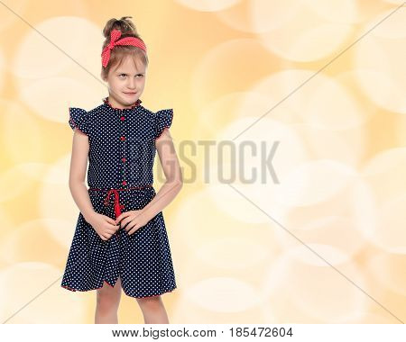 Cute little girl in a short blue dress with polka dots. With a red bandage on his head.Close-up.Brown festive, Christmas background with white snowflakes, circles.