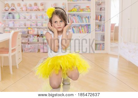 Pretty little blonde girl in a short bright yellow skirt and white blouse.She kneels and gently looking at the camera with folded hands near the face.In the children's room.