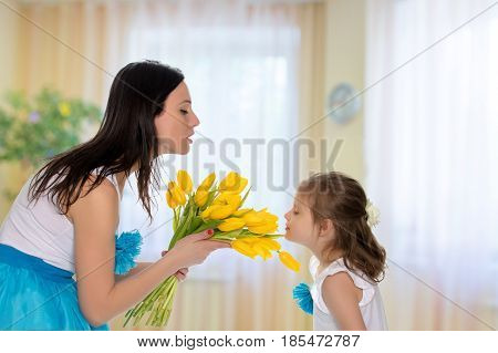Beautiful young mother and little daughter in the same blue long skirts tutus , standing sideways to the camera , admiring the bouquet of yellow tulips.Little girl enjoying the smell of flowers.In the children's room.
