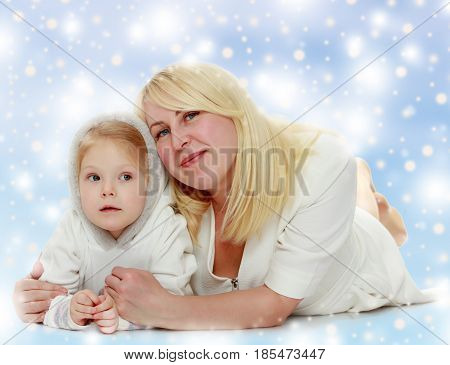 Happy family mother and little daughter lying on the floor and laughing directly into the camera.Blue Christmas festive background with white snowflakes.
