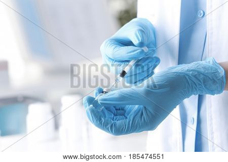 Female doctor with syringe and medicine in clinic, closeup