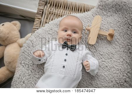 Cute little baby in stylish outfit lying on soft blanket