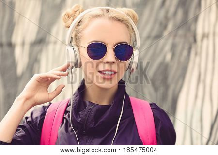 Beautiful girl listening music on street