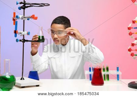 School boy sitting at workplace and controlling experiment in chemistry class