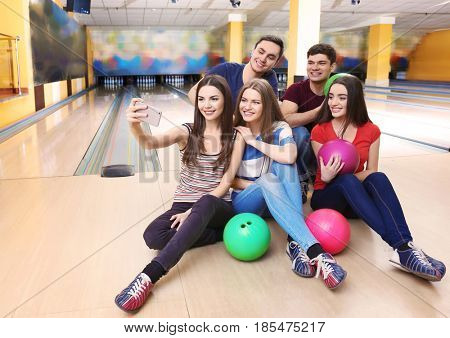 Friends taking selfie in bowling club