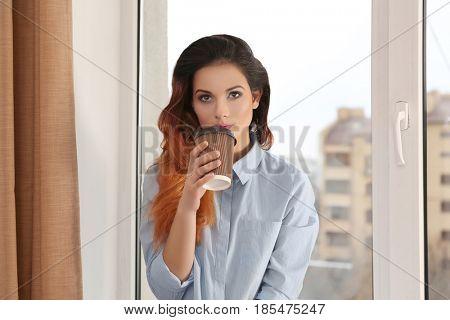 Beautiful young woman drinking coffee near window at home