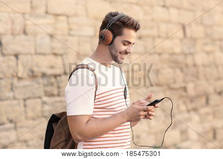 Handsome man with headphones listening music on brick wall background