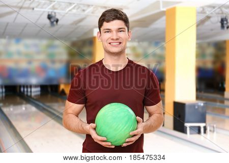 Handsome young man with ball in bowling club