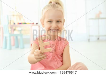 Cute little girl with letter E at home