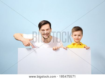Handsome man and his son with poster on color background