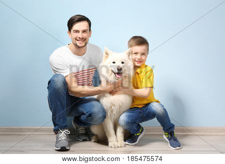 Handsome man, his son and dog near color wall