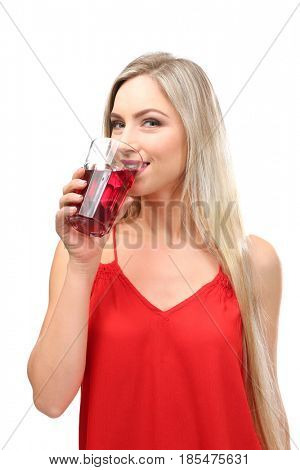 Beautiful young woman drinking fresh juice on white background