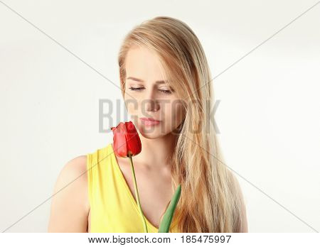 Beautiful young woman with tulip on white background