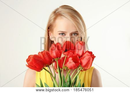 Beautiful young woman with bouquet of tulips on white background