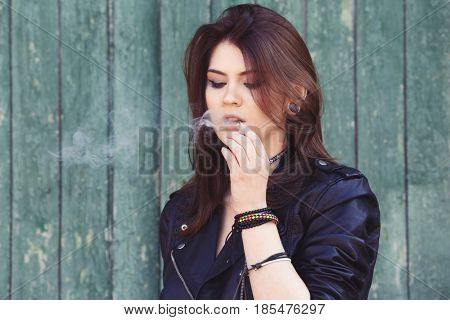 Beautiful young woman smoking weed near wooden fence outdoors