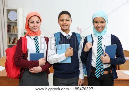 Schoolchildren standing in classroom with books