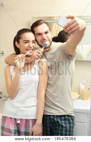 Young happy couple taking selfie while brushing teeth in bathroom
