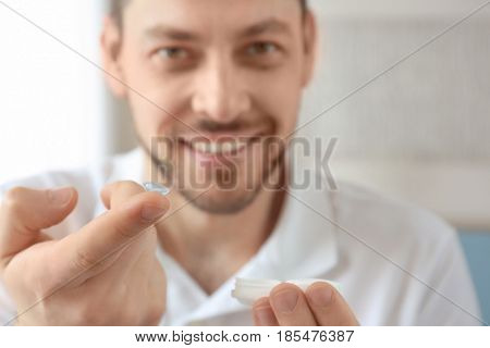 Hands of young man with contact lenses, closeup