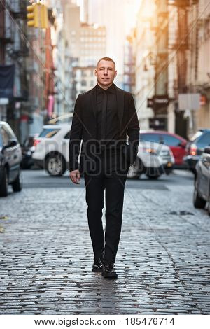 Full-length portrait of adult businessman walking on city street wearing black suit.