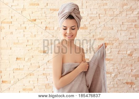 Beautiful young woman after shower standing near brick wall