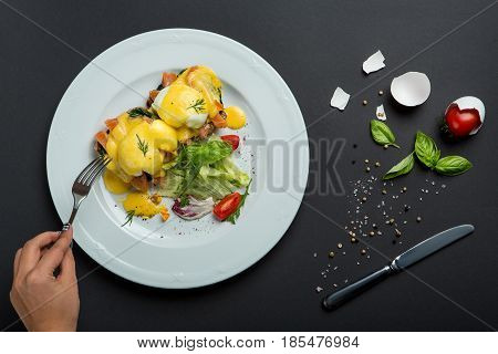 Top view of healthy breakfast with poached eggs royale, benedict with salmon and green salad on black background.