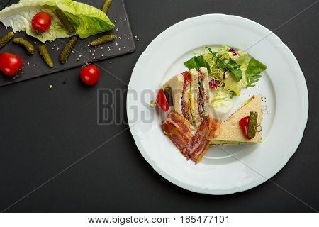 Sandwich with bacon and vegetables on black background. breakfast or lunch dish. For a restaurant logo. Top view photo.