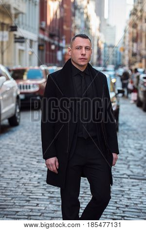 Adult successful businessman crossing city street wearing suit and jacket